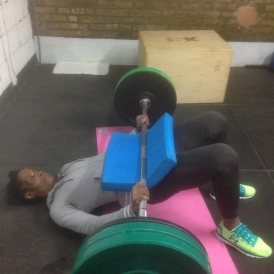 Victoria demonstrating 80kg weighted glute bridges.